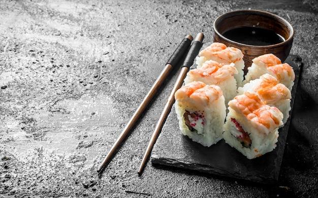 Świeże sushi rolki z krewetkami na stojaku z sosem sojowym i pałeczkami. na czarnym tle rustykalnym