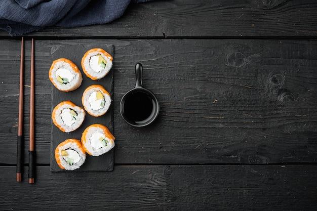 Świeże sushi z zestawem wasabi i imbirem, na czarnym drewnianym stole
