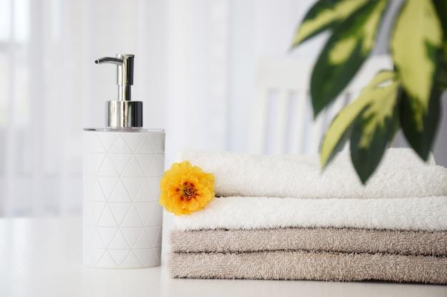 Świeże szare i białe ręczniki złożone na białym stole, kwiat pomarańczy i pojemnik na płyn z zielonymi liśćmi i tiulowym okienkiem na tle.