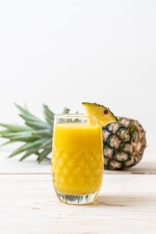 Świeże szkło smoothie ananas na stół z drewna - zdrowy napój