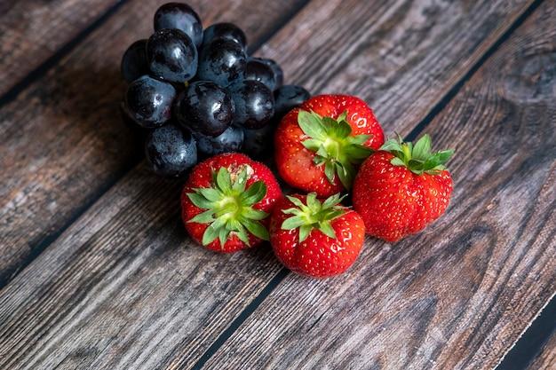 Świeże szkockie truskawki i czarne winogrona na drewnianym stole