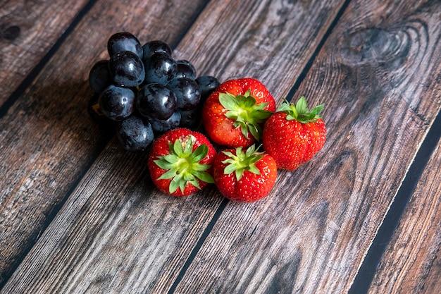 Świeże szkockie truskawki i czarne winogrona na drewnianym stole.