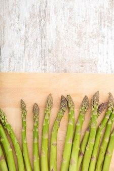 Świeże szparagi na drewnianej tabliczce.