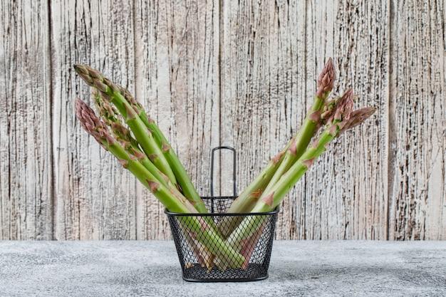 Świeże szparagi wyrastają z czarnej durszlaka na nieczysty szarej i drewnianej ścianie