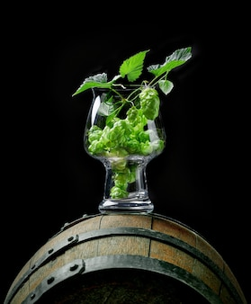 Świeże szyszki chmielowe w szkle do piwa rzemieślniczego na starej drewnianej beczce