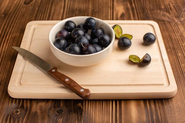 Świeże tarniny wewnątrz płyty na drewnianym biurku owoce jagodowe świeże kwaśne