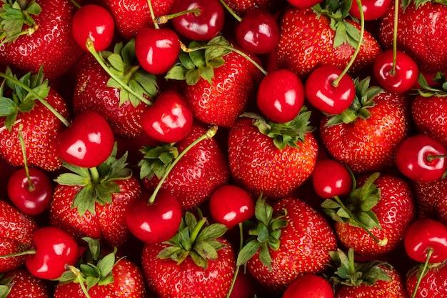 Świeże tło, świeżo zebrane truskawki i wiśnie, tło z sezonowymi jagodami i owocami.