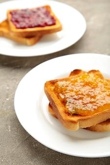 Świeże tosty z masłem i różnymi dżemami na szarym stole. zdjęcie pionowe