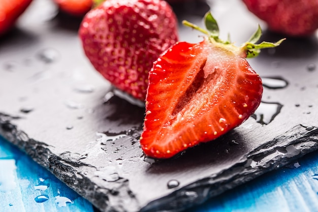 Świeże truskawki dojrzałe myte wodą na niebieskim stole.