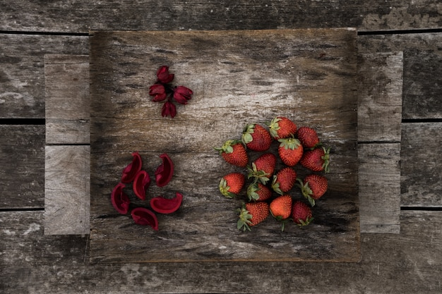 Świeże truskawki i czerwone płatki kwiatów na powierzchni drewnianych