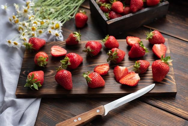 Świeże truskawki na drewnianym stole w kuchni z bukietem stokrotek i tekstyliów, koncepcja lato, z bliska.
