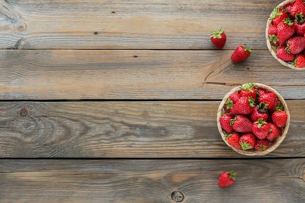 Świeże truskawki na koszcie narzutu. makieta zdrowej żywności na drewnianym stole