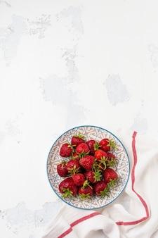 Świeże truskawki na lekkim talerzu na białym starym betonie