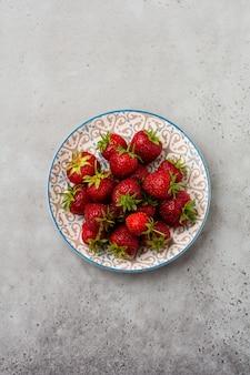 Świeże truskawki na lekkim talerzu na szarym starym betonie
