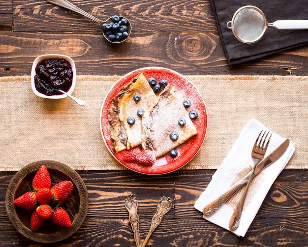 Świeże truskawki naleśniki lub naleśniki z jagodami i czekoladą