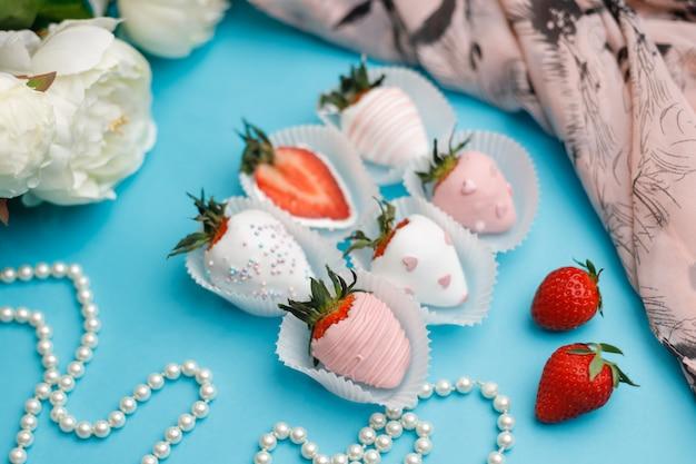 Świeże truskawki pokryte białą i różową czekoladą leżą na turkusie