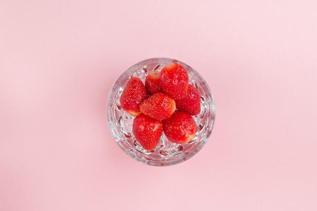 Świeże truskawki w blenderze, aby przygotować zdrowy koktajl mleczny na pastelowo różowej powierzchni. widok z góry, zdrowe odżywianie i koncepcja diety, koncepcja zasadowa, wegetariańska.