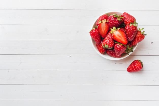 Świeże truskawki w ceramicznym talerzu na białym stole. skopiuj miejsce.