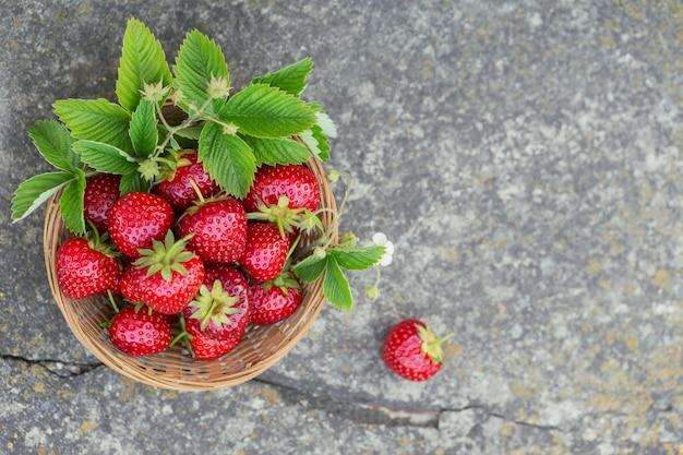 Świeże truskawki w koszu na rustykalnym tle betonu widok z góry. makieta zdrowej żywności na szarym stole