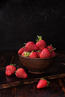 Świeże truskawki w misce na ciemnym tle drewnianych, koncepcja lato, z bliska.