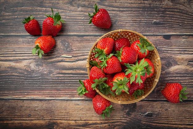 Świeże truskawki w misce na drewnianym stole