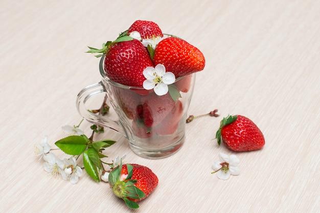 Świeże truskawki w szklanej filiżance na drewnianym stole