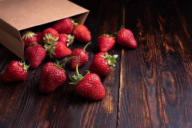 Świeże truskawki wypadające z papierowej torby na ciemnym tle drewnianych, koncepcja lato, z bliska.