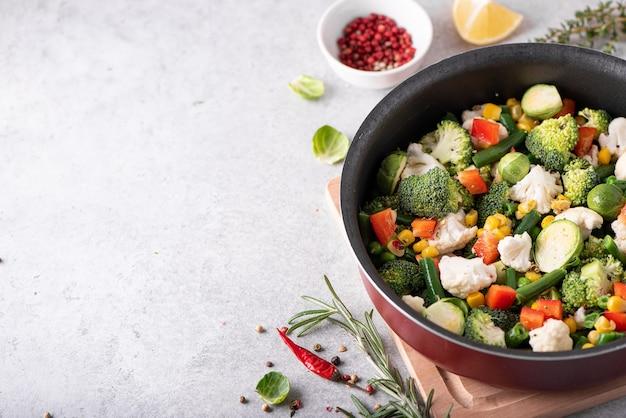Świeże warzywa - brokuły, fasolka szparagowa, groszek, kalafior duszony w rondelku, widok z góry