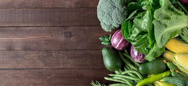 Świeże warzywa ekologiczne: brokuły, awokado, kukurydza, sałata rzymska, szparagi, bakłażan na drewnianym stole, widok z góry.