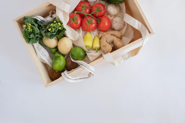 Świeże warzywa i owoce w drewnianym pudełku dla zdrowej diety wegańskiej i dostawy produktu.