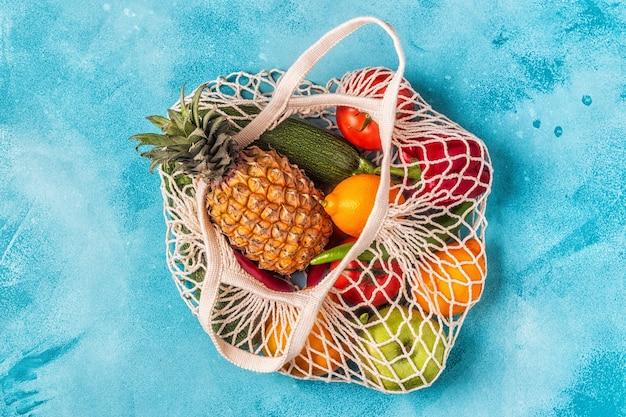 Świeże warzywa i owoce w siatce worka, widok z góry.