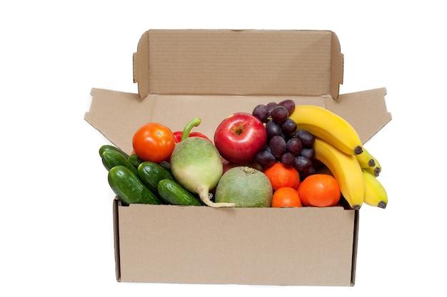 Świeże warzywa i owoce w tekturowym pudełku na białym tle