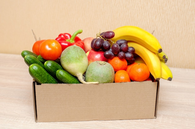 Świeże warzywa i owoce w tekturowym pudełku na drewnianym stole