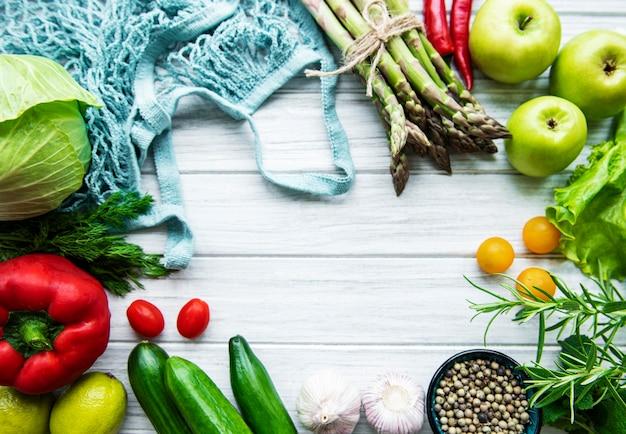 Świeże warzywa i owoce w worku sznurkowym na białej drewnianej powierzchni. zdrowy tryb życia. widok z góry. zero marnowania.