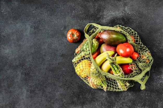 Świeże warzywa i owoce w zielonej torbie ze sznurka. bez plastiku, tylko naturalne materiały i naturalne produkty.