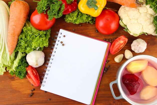 Świeże warzywa i przyprawy oraz papier do notatek na drewnianym stole