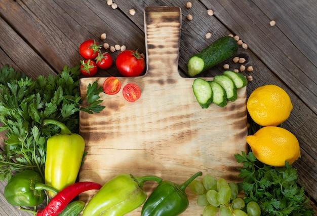 Świeże warzywa i surowe składniki do gotowania wokół drewnianej deski do krojenia na rustykalnym widoku z góry, miejsce na tekst