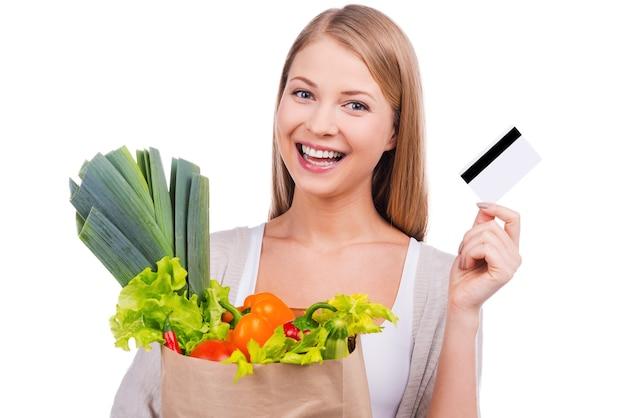 Świeże warzywa kupuję codziennie. piękna młoda kobieta niosąca torbę na zakupy pełną artykułów spożywczych i pokazująca swoją kartę kredytową, stojąc na białym tle