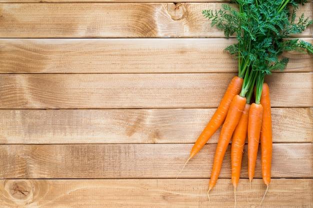 Świeże warzywa marchewkowe z liśćmi na drewnianym