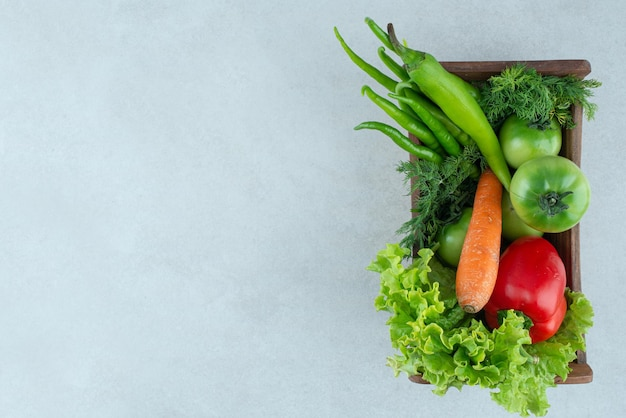 Świeże warzywa mieszane w drewnianym pudełku.
