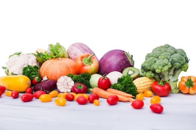 Świeże warzywa na drewnianym stole. na białym tle