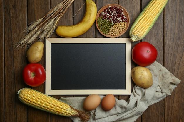 Świeże warzywa organiczne, owoce, jaja, fasola i corns z tablicą na zabytkowe drewniane tabeli