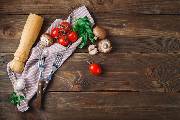 Świeże warzywa - pomidory, czosnek, pieczarki, pietruszka, pieprzniczka, widelce i serwetka na drewniane tła. miejsce na tekst. widok z góry