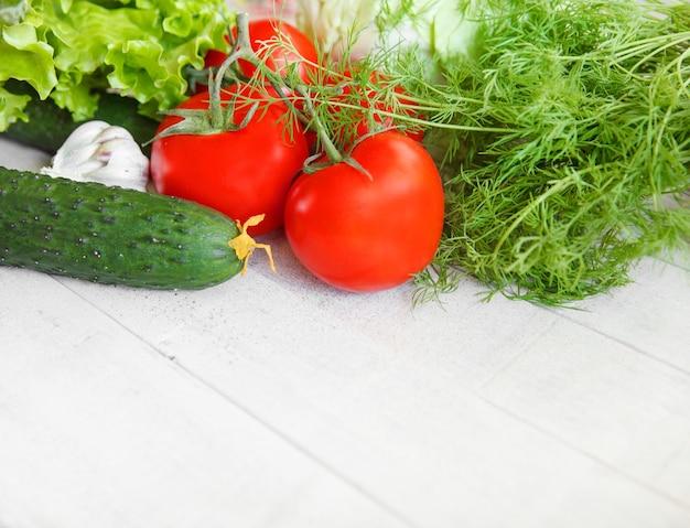 Świeże warzywa pomidory na gałęzi ogórki z koperkiem na białym tle