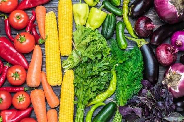 Świeże warzywa posortowane według koloru - kukurydza, marchewka, zielona sałata, kolendra, ogórek, bazylia, koper