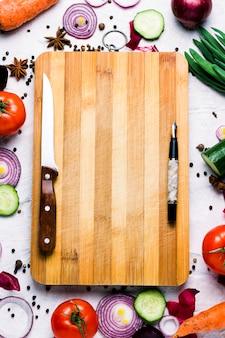 Świeże warzywa rolnicze wokół deski do krojenia, długopis, nóż z miejsca kopiowania. pomidory, krążki czerwonej cebuli, przyprawy, ogórek, marchew. scena gotowania