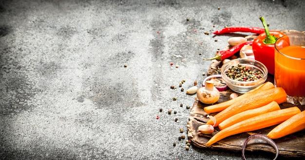 Świeże warzywa. świeże warzywa z przyprawami, ziołami i sokiem z marchwi na rustykalnym stole.