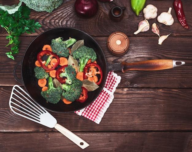 Świeże warzywa w czarnej okrągłej patelni