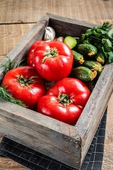 Świeże warzywa w drewnianym pudełku, czerwone pomidory, zielone ogórki z ziołami. drewniane tło. widok z góry.