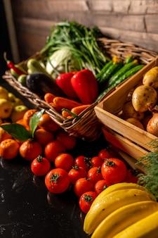 Świeże warzywa w drewnianym pudełku na drewnianym tle. rynek owoców i warzyw